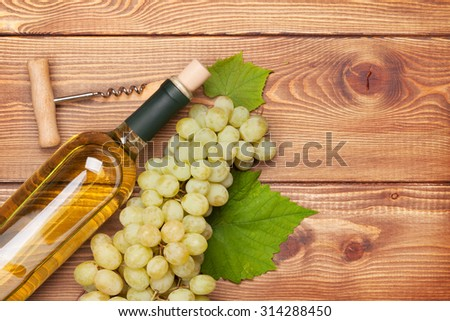 White wine bottle and bunch of white grapes on wooden table background with copy space - stock photo