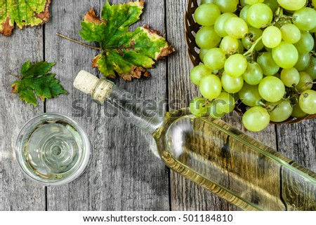 White wine bottle and glass of wine from grapes, flat lay, overhead