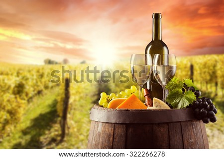 White wine bottle and glass on wooden keg with various kind of cheese. Vineyard on background - stock photo