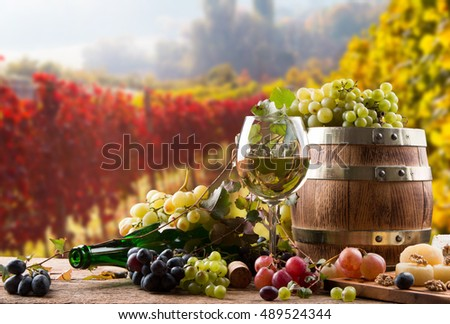 white wine bottle and wine glass, wooden barrel with nature background
