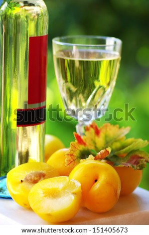 White wine bottle, glass and plums