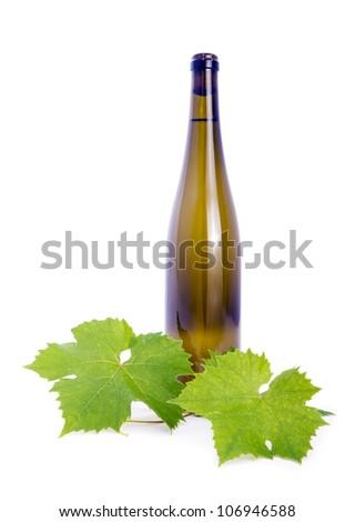 White wine, bottle of grape leaves. - stock photo