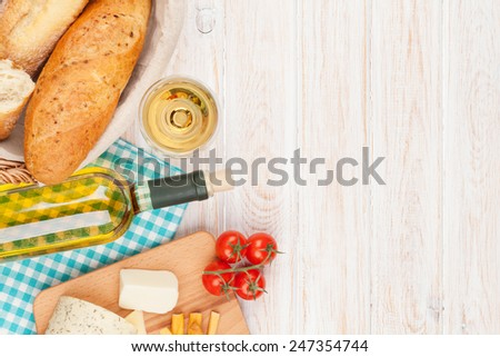 White wine, cheese and bread on white wooden table background with copy space - stock photo