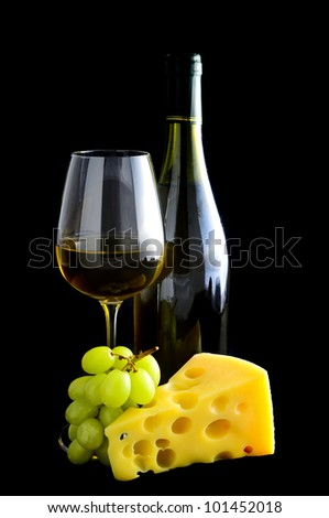 white wine, cheese and grapes on a black background