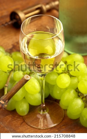 white wine glass and grapes on wooden table - stock photo