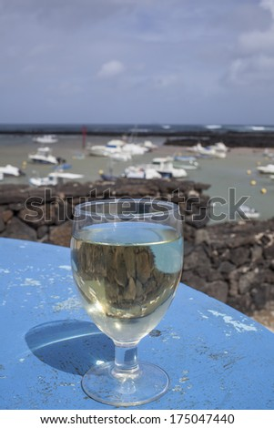 White wine glass in front of marina in Lanzarote, Spain  - stock photo