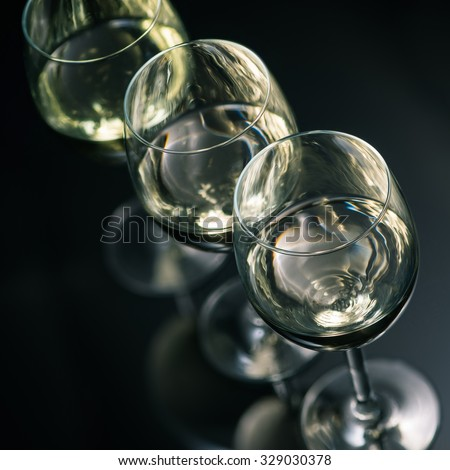 White wine glasses on dark glossy background - stock photo