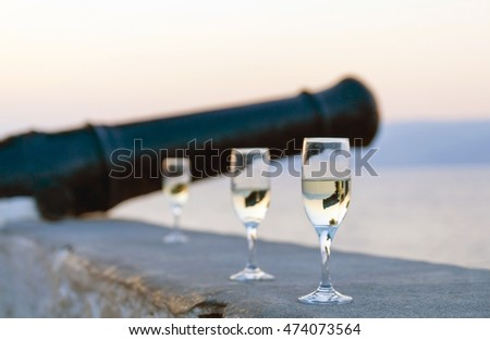 White wine glasses outdoors on the stone plate near old cannon in sea sunset time