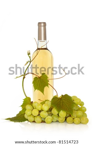 White wine in a bottle with fresh grapes on the vine with leaf sprigs isolated over white background.