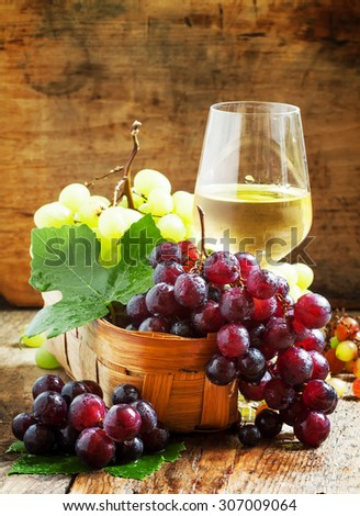 White wine in a glass and green and red grapes in a wicker basket, still life in a rustic style, toned image, selective focus - stock photo