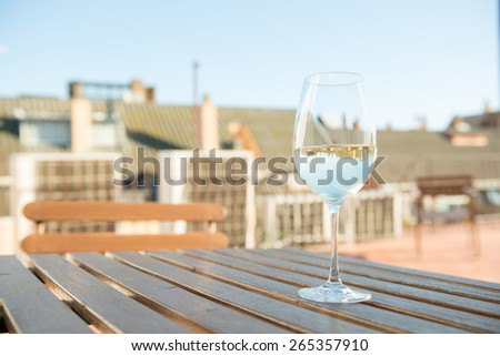 White wine in a glass on an open terrace with the reflection of background houses in wine  - stock photo