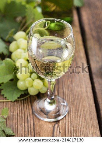 White Wine in a glass with fresh grapes (on wooden background)