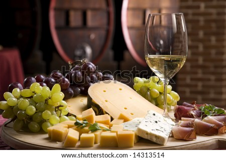 White wine in fine glass with cheese and grape - stock photo