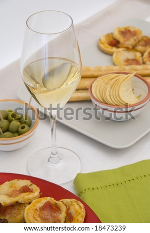 White wine in fine glass with mini pizzas and green olives