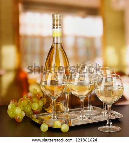 White wine in glass and bottle on room background - stock photo