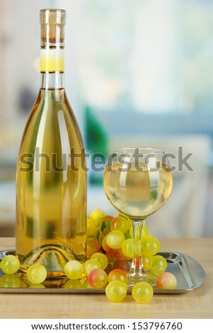 White wine in glass with bottle on salver on room background - stock photo