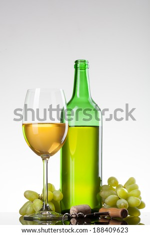 White wine in glass with grape and bottle isolated on white