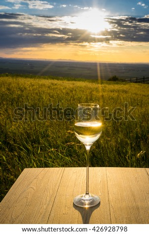 White wine in sunset, countryside with wineglass - stock photo