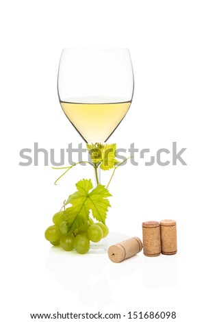 White wine in wine glass with green grapes, vine leaves and various wine corks isolated on white background. Luxurious wine still life. - stock photo