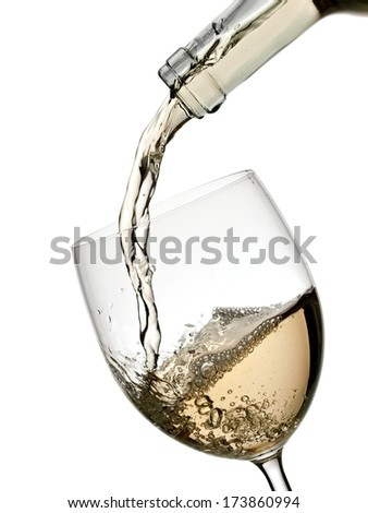 White wine pouring in a glass from a bottle - stock photo