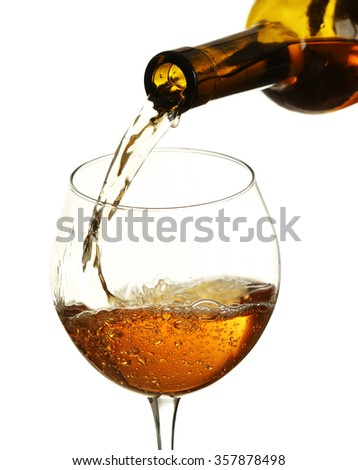 White wine pouring in glass, isolated on white