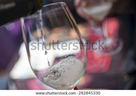 White wine pouring in the glass  - stock photo