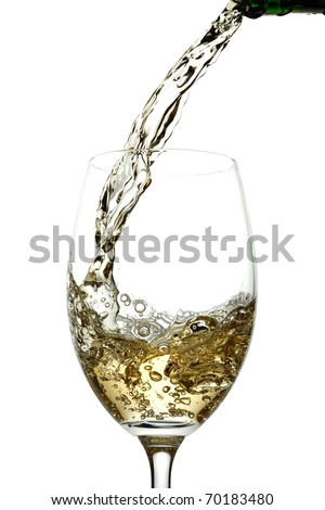 White wine pouring into glass - stock photo