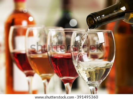 White wine pouring into glasses, closeup - stock photo
