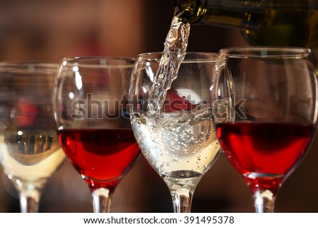 White wine pouring into wine glass, closeup - stock photo