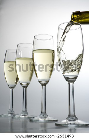 White wine pours into one of four glasses