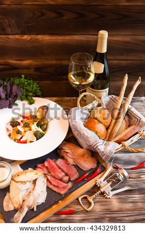 White wine, salad of snack are served on a table at restaurant. Romantic dinner