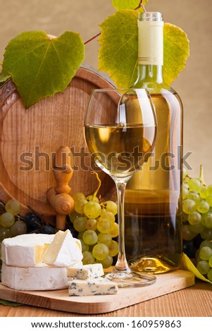 White wine with cheese and blue grape snack in front of small barrel and vine leaves