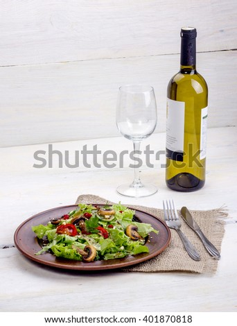 White wine with vegetable salad of greens, mushrooms and tomatoes with seasoning - stock photo