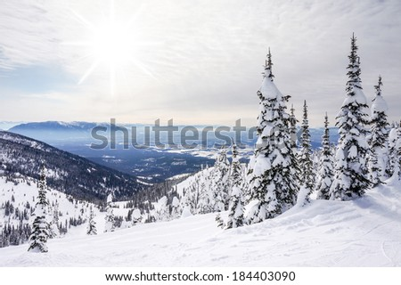 White winter landscape against the sun with fluffy clouds in Whitefish, Montana, overlooking Glacier National Park. - stock photo