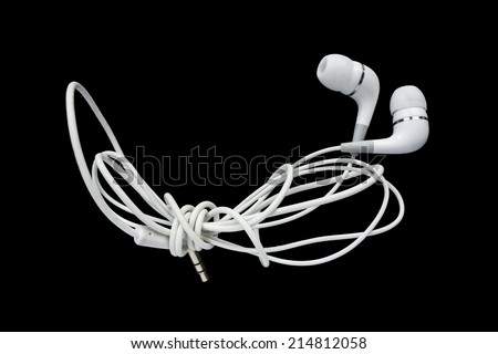 White wired earphones isolated over black - stock photo