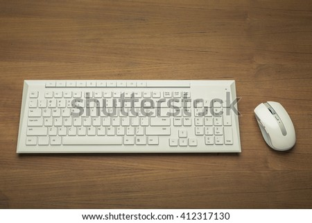 White wireless computer mouse and keyboard on wooden table - stock photo