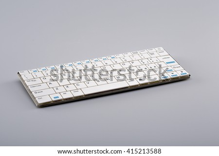 White wireless keyboard on gray background