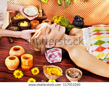 White woman getting facial mask in tropical beauty spa. - stock photo