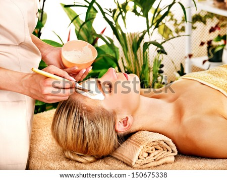 White woman getting facial mask in tropical beauty spa.