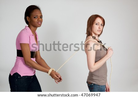 White woman leading a bound black woman - stock photo