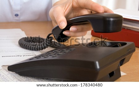 White woman's hand is reaching for a phone - stock photo