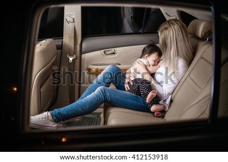 White woman with a child of one year in the light leather car interior preparing to rest and sleep - stock photo