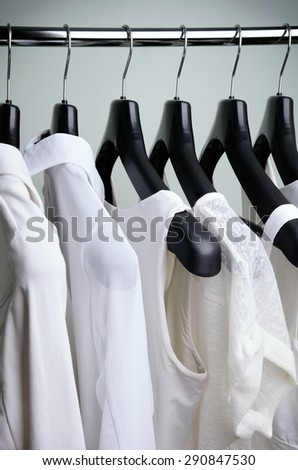 white women's clothing hanging. side view, vertical frame - stock photo