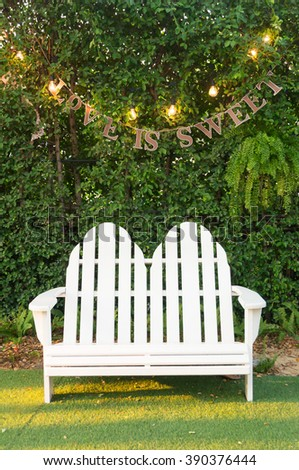 White wood bench in garden with light bulb  and text Love is sweet. sunset light.