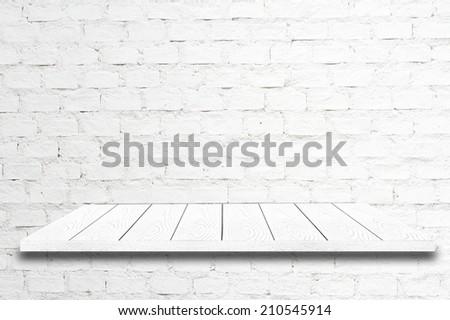 White wood shelf on white brick wall. - stock photo
