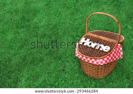White Wood Sign Home On The Picnic Basket, Bright Summer Green Grass In The Background - stock photo