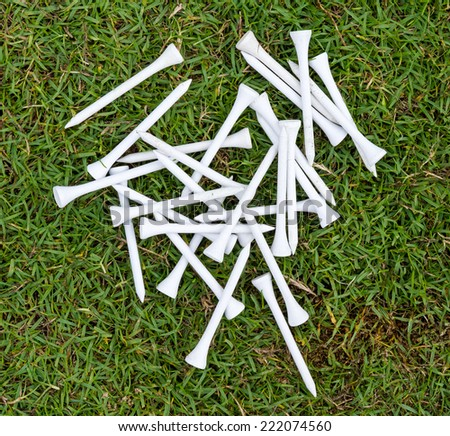 White wood tee on grass in golf course for swing practice. - stock photo