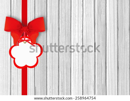 white wooden background with beautiful red bow with tag - stock photo