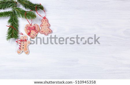 White wooden background with cookies hanging from fir branches on upper left corner.