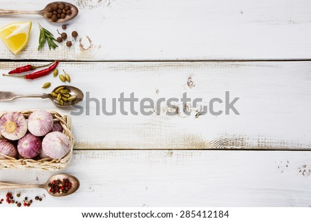 White wooden background with garlic, herbs and spices selection. Space for text. Cooking, food or health concept. - stock photo
